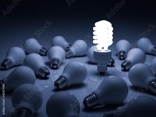 Photo  Lit energy saving lightbulb amongst unlit incandescent bulbs