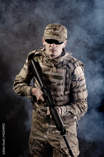 Soldier with a rifle on a black background Canvas Print