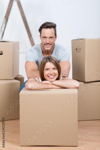 Fototapeta lächelndes paar sitzt zwischen umzugskartons obraz na płótnie