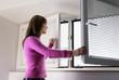 canvas print picture - Frau öffnet ein Fenster