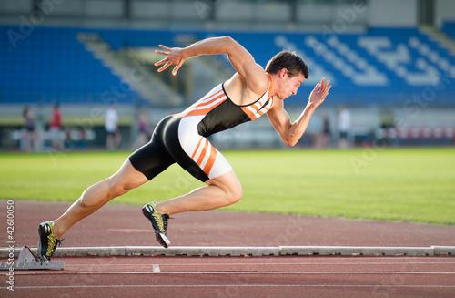 Fotografía  Sprinter dejando la salida de la pista de atletismo. Explosivo