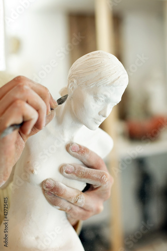 Fotografie, Obraz  Hands of the sculptor with a statuette and a tool