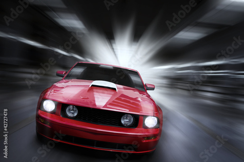 Luxury red sport car speeding in a underground parking