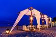 Leinwanddruck Bild - Romantic set up dinner on the beach, twilight time