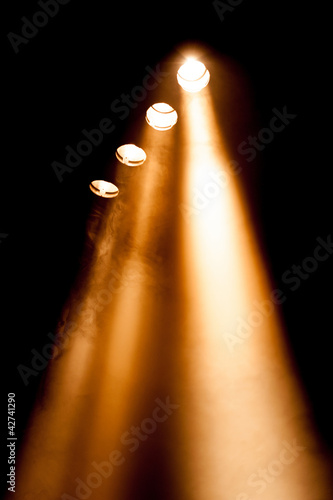 Foto op Canvas Licht, schaduw Four spotlights with orange beams