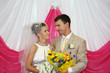 Happy groom and beautiful bride with flowers look at other indoo
