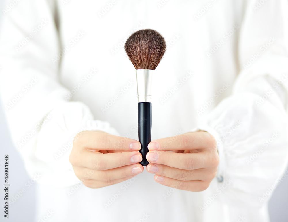 Fototapeta Kobieta trzymająca w dłoniach akcesoria do makijażu