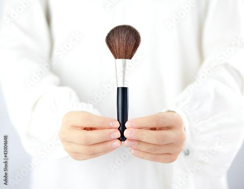 Fototapeta Kobieta trzymająca w dłoniach akcesoria do makijażu obraz