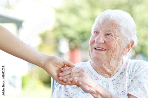 Láminas  Senior woman holding hands with caretaker