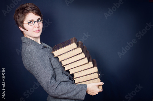Fotografering  business woman holding a heavy stack of books in hands
