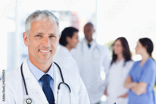 Fotografia  Mature doctor standing upright while waiting for his team