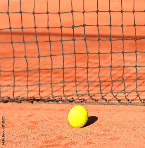 tennis ball close to net on clay court