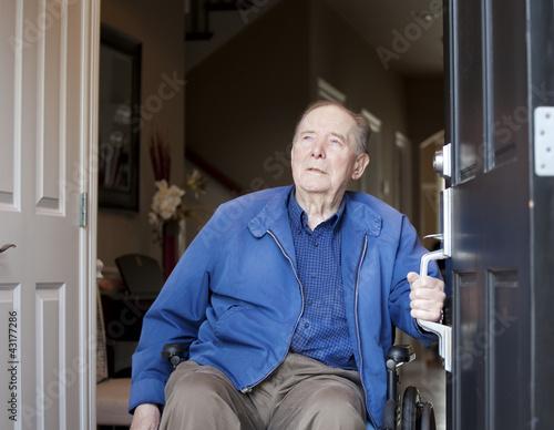 Fotografie, Obraz  Elderly man in wheelchair at his front door, looking up