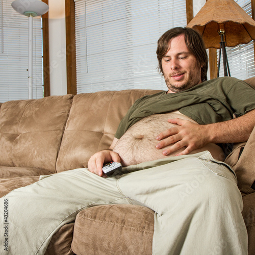 Photo  Heavy set man on the couch admiring his stomach