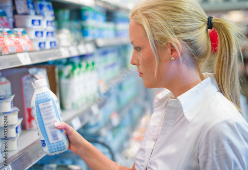 Fotografie, Obraz  Frau kauft Milch im Supermarkt