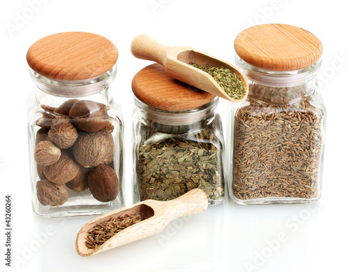 Tuinposter Kruiden 2 jars and wooden spoons with parsley, nutmeg and cumin isolated