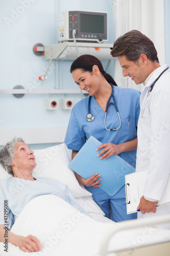Fotografia  Elderly patient talking to a doctor and a nurse