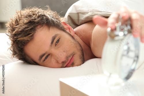 Man in bed turning off alarm Wallpaper Mural
