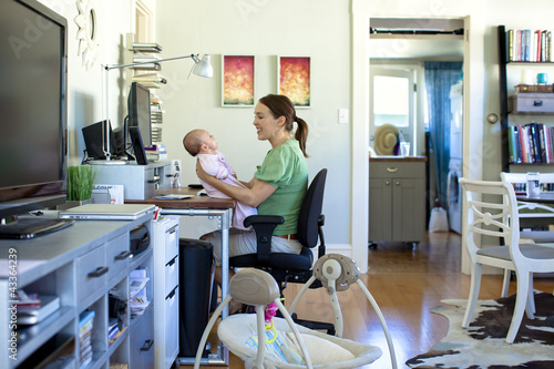 Fototapety, obrazy: Caucasian mother working in home office and holding baby