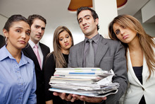 Frustrated Hispanic Business People With Pile Of Paperwork