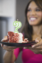 Mixed Race Woman Holding Cake With Question Mark Candle