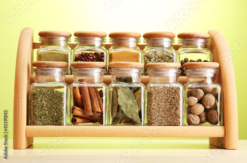 Photo Stands Herbs 2 powder spices in glass jars on wooden shelf on green background
