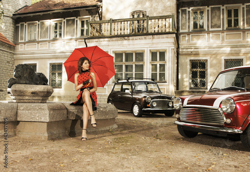 Papiers peints Rouge, noir, blanc A vintage fashion shoot with a young woman holding an umbrella
