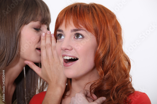 Photo Woman whispering into another woman's ear