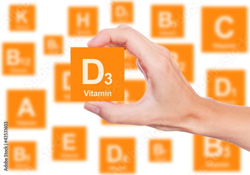 Fotografia  Hand holds a box of vitamin D3