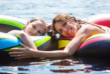 Mother And Daughter Floating On A Lake