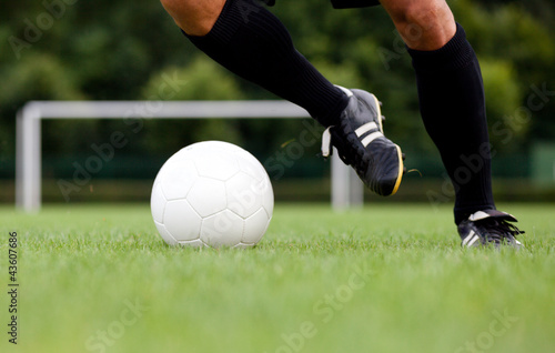 Detailed view of a footballer / soccer player dribbling the ball