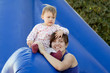 happy mother with toddler on slide