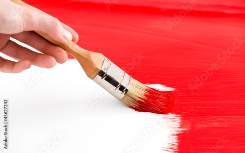 Painting with red colored ink and brush on white