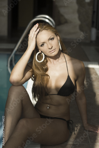 Sexy indian woman in black bikini by dark pool - Buy this stock