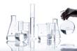 Leinwandbild Motiv Set of empty glass flasks with a hand holds one of them