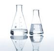 Leinwandbild Motiv Two laboratory flasks with a clear liquid, isolated