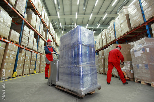 Warehousing -  Two workers in uniforms  working in storehouse Canvas Print