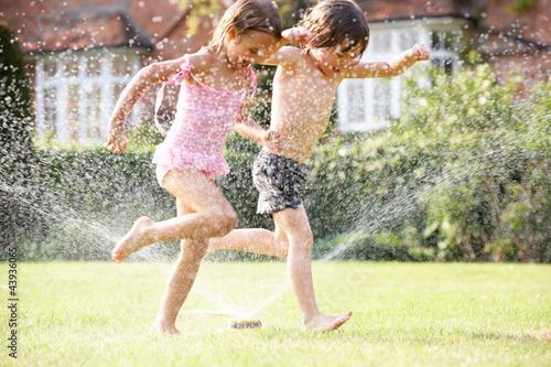 Obraz Two Children Running Through Garden Sprinkler - fototapety do salonu