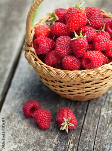 Obraz fresh raspberry in a basket on wooden table - fototapety do salonu