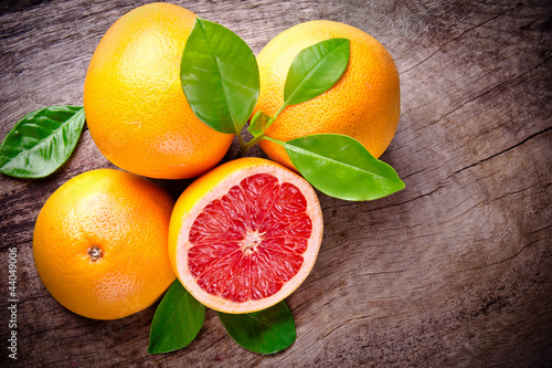 Obraz Freshly harvested grapefruit on wooden background - fototapety do salonu