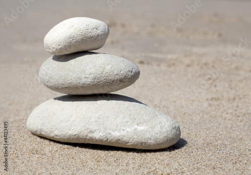 Photo sur Plexiglas Zen pierres a sable galets blanc en équilibre sur sable blanc