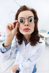 Very serious dentist's assistant uses medical spectacles