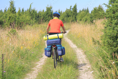 Photo Stands Cycling Cyclist on a cart-road between junipers