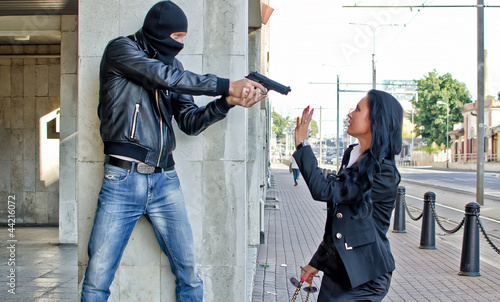 Fotografía  Bandit with a gun threatening young woman in the street