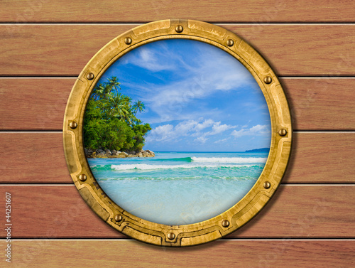 ship porthole with tropical island behind