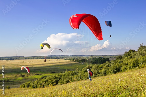 Deurstickers Luchtsport Multiple paragliders soar in the air amid wondrous landscape