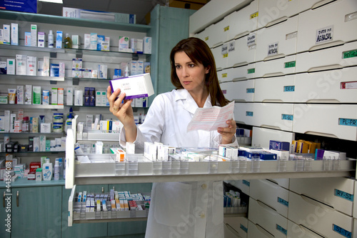 Fotobehang Apotheek pharmacist woman looking for medicine