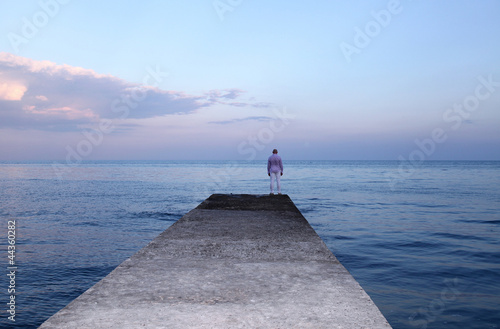 Cadres-photo bureau Lavende Lonely man watching the sunset on the pier