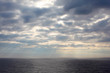 gray clouds over dark and cold sea;