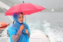 Beautiful Woman Dressed In Blue Raincoat Holds Pink Umbrella